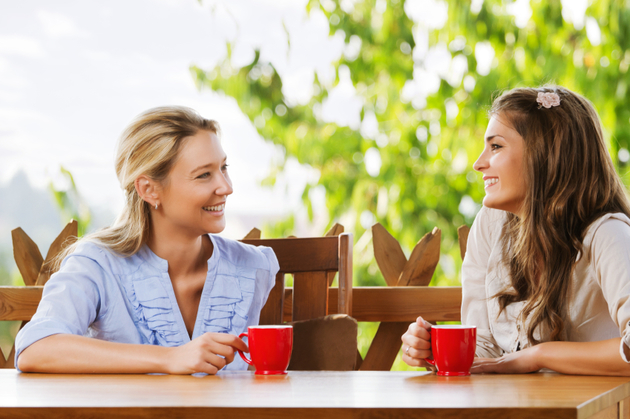 Two friends chatting with coffee on balcony